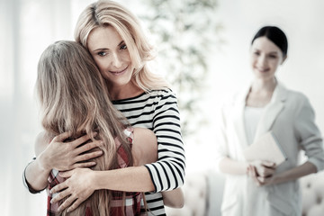 Best daughter. Satisfied pretty blonde woman standing in the spacious room hugging her daughter and smiling.