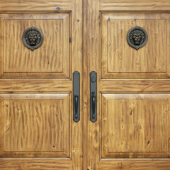 Close up detail of formal wooden front entry doors with bronze hardware and lion head medallions. Exclusive, elegant, upscale, luxury home real estate with high quality building materials.