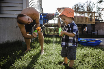 Playful father spraying water with squirt guns on son while playing at backyard