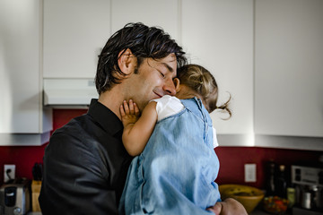 Smiling father embracing daughter while carrying her in kitchen at home