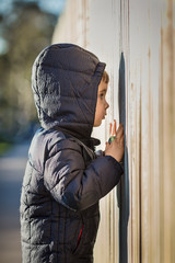 Side view of curious boy wearing hooded jacket while peeking through wooden fence