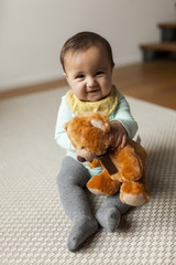 Portrait of cute baby girl holding teddy bear while sitting on carpet at home