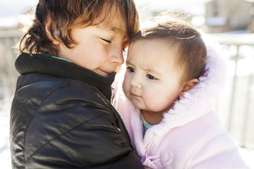 Close-up of brother carrying cute sister while standing outdoors during winter