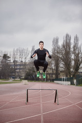 Portrait of male athlete exercising on sports track against cloudy sky