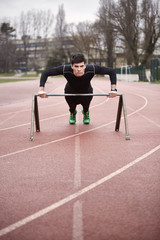 Portrait of male athlete exercising on sports track