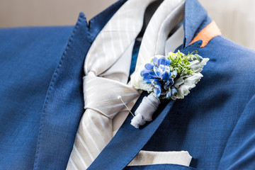Men's new marine navy blue suit and tie groom closeup with flower boutonniere, pin getting ready wedding preparation isolated, pocket handkerchief