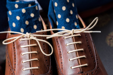 Men's leather new brown shoes closeup still life isolated with blue polka dot socks, shoelaces laces tied, wedding or interview preparation in room