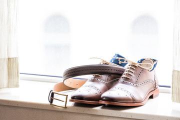 Men's leather new brown shoes closeup still life isolated with blue polka dot socks, watch, shoelaces laces tied, wedding or interview preparation, belt on windowsill in room with window blinds