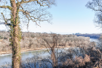 Overlook of Potomac River frozen surface in winter landscape, bare trees with Washington DC neighborhood houses, park, close to Georgetown, Arlington, Virginia in capital city