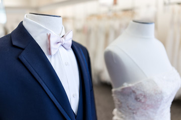 Closeup of bride and groom mannequin in blue, pink wedding attire suit, butterfly necktie, tie and white gown in boutique store, shop