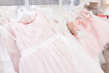 Many wedding flower girl party dresses in boutique discount store, pink garments hanging on rack hangers row closeup with white lace, tulle, design