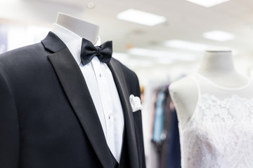 Closeup of bride and groom mannequin in black wedding attire suit, butterfly necktie, tie and white gown in boutique store, shop, handkerchief
