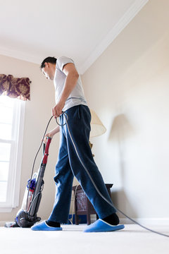Young man house husband stay at home dad vacuuming using vacuum on carpet floor inside interior of house living room by window, standing walking in slippers, domestic life