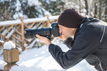 One young man photographer with camera, long telephoto lens taking pictures of wildlife in snow winter backyard deck in jacket, hat