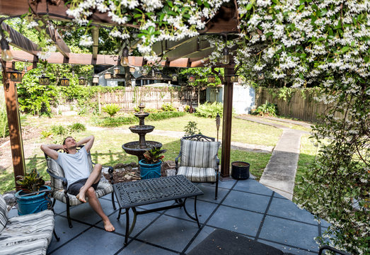 Young man lying down on patio lounge chair in outdoor spring flower garden in backyard porch of home happy smiling in zen with fountain, pergola canopy gazebo, table, plants, sofa