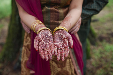 Midsection of bride showing henna tattoo while standing with bride outdoors