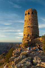 Visitors look out at the Grand Canyon beside the stone Watchtower at sunset.