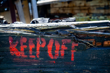 Keep off sign on Rotting Wooden Structure of an old cargo  barge