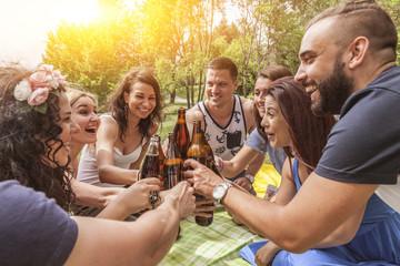 freunde stoßen auf ihre freundschaft an. anstoßen mit bier in flaschen. fokus auf mann in der mitte