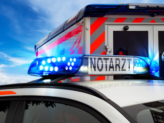 Teilansicht Feuerwehreinsatzfahrzeug mit Blaulicht und Notarztfahrzeug