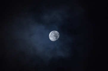 White round moon on a black background of night sky among the clouds, full moon.