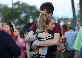 Students embrace during a vigil held at the Texas First Bank after a shooting left several people dead at Santa Fe High School in Santa Fe, Texas