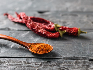 Wooden spoon with ground red pepper and chilli peppers on black rustic table.