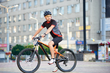 Male professional bicyclist in cycling sportswear and helmet riding bike, looking in distance. Man resting and relaxing after work, training on bicycle on city streets. Concept of healthy lifestyle