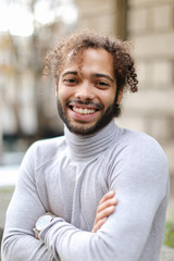 Portrait of half african handsome boy wearing grey turtleneck sweater and having curly brown hair. Concept of fashionable look.