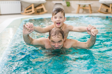 grandfather having fun with his grandson in the pool