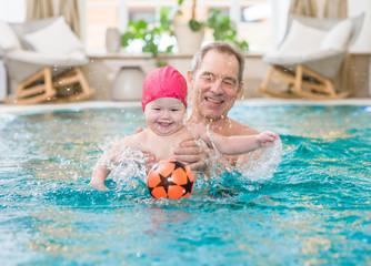 grandpa fun playing ball with granddaughter in the pool