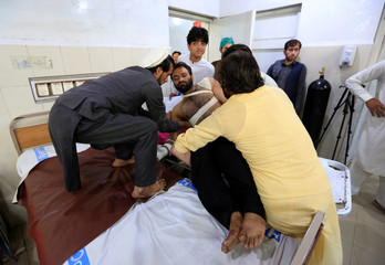 An injured man receives treatment in a hospital, after blasts at a sports stadium, in Jalalabad city, Afghanistan