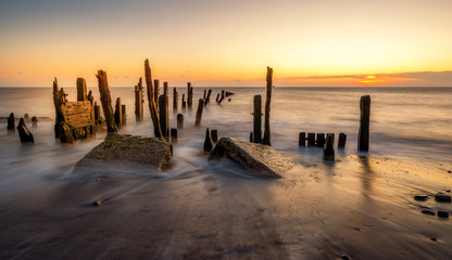 Morning sunlight hits old wooden posts on the beach at Spurn Point near Hull, Yorkshire, England.