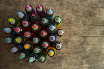 Multi tattoo ink bottles on wooden table.
