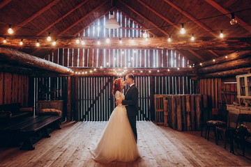 stylish groom and happy bride hugging under retro bulbs lights in wooden barn. rustic wedding concept, space for text. newlyweds couple embracing, sensual romantic moment