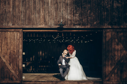 rustic wedding couple posing and hugging at background of wooden barn with retro lights, space for text. happy stylish bride and groom at wood wall in country, bohemian newlyweds