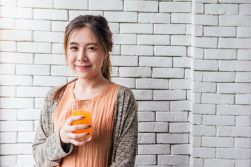 Lovely Asian Woman Relaxing in Cozy House with Orange Juice Glass. Portrait of Young Female, Looking at Camera