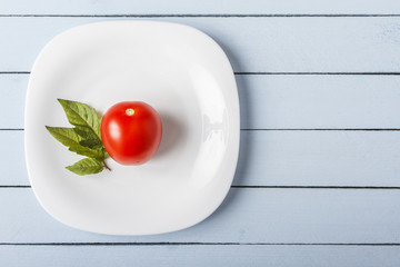 Fresh organic tomato and tomato leaves on white plate. Top view on blue wooden table with copy space. Healthy food concept