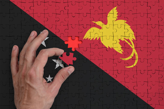 Papua New Guinea flag  is depicted on a puzzle, which the man's hand completes to fold