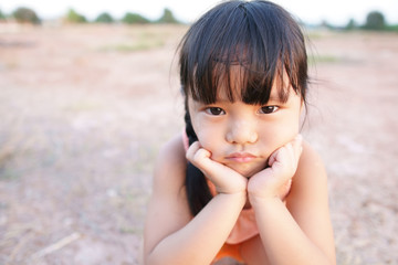 Asian children cute or unhappy kid girl and country child poor with make face frown and angry or sad with touchy wear traditional top or sleeveless shirt sit on arid soil for agriculture at home