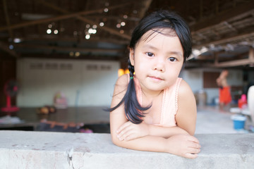 Asian children cute or kid girl and country child poor with smile wear traditional top or sleeveless shirt at old wooden home and terrace