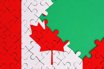 Canada flag  is depicted on a completed jigsaw puzzle with free green copy space on the right side