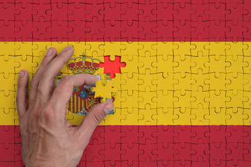 Spain flag  is depicted on a puzzle, which the man's hand completes to fold