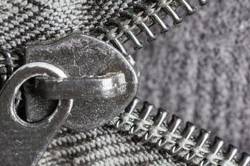 Unzipped brass zipper closeup on blue jeans