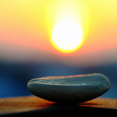 stack of pebble on yellow sun background