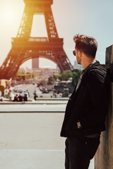 Young man looks to the tour eiffel. The bearded man is dressed silk in his sunglasses