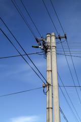 High voltage pole scene with blue sky