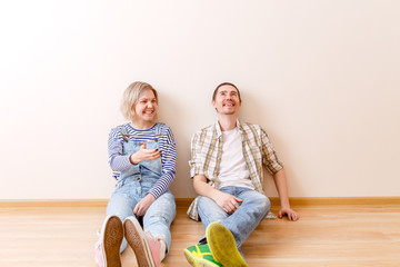 Photo of young married couple sitting on floor among cardboard boxes