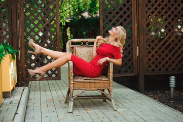 Fashionable attractive blonde woman in red dress sitting on chair.