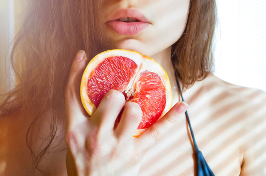 beautiful young sexy woman in bikini holding two fingers on grapefruit  on the background of her lips. Sex concept.